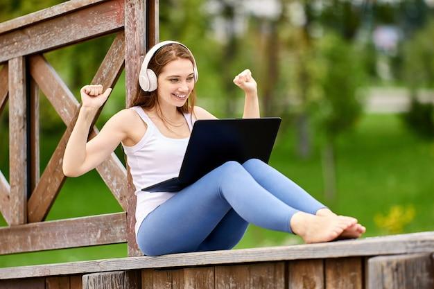 Kobieta przed laptopem czekająca na dobre wieści siedzi na drewnianym płocie w publicznym parku
