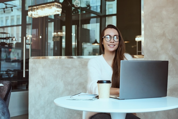 Kobieta przedsiębiorca pracuje z kawiarni i rozmawia przez telefon komórkowy ze słuchawkami