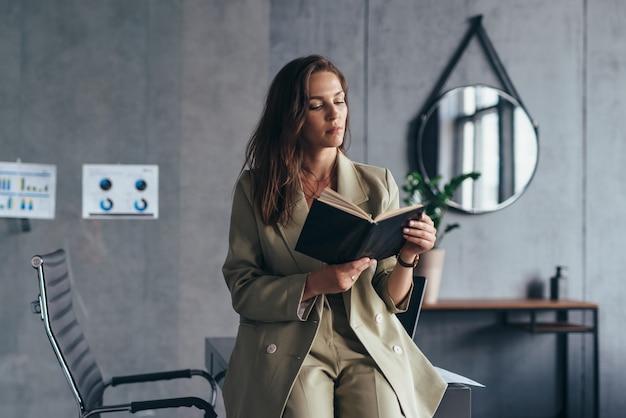 Kobieta przedsiębiorca w pracy czytanie notatek w terminarzu.