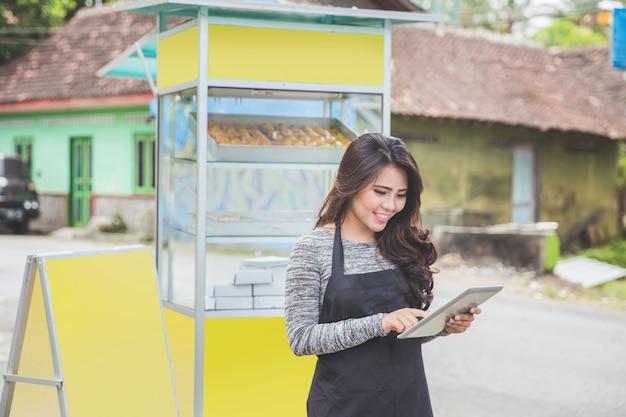Kobieta przedsiębiorca z nowo otwartego stoiska żywności