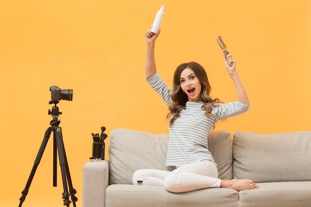 Kobieta przedstawia włosianych produkty na kamerze