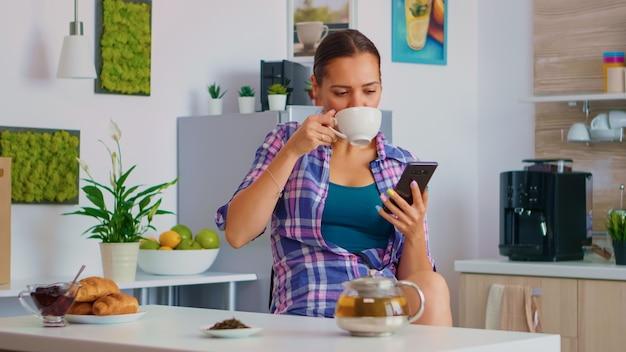 Kobieta przeglądająca na smartfonie podczas picia zielonej herbaty, rano podczas śniadania. trzymanie urządzenia telefonicznego z ekranem dotykowym za pomocą przewijania w technologii internetowej, wyszukiwania na inteligentnym gadżecie.