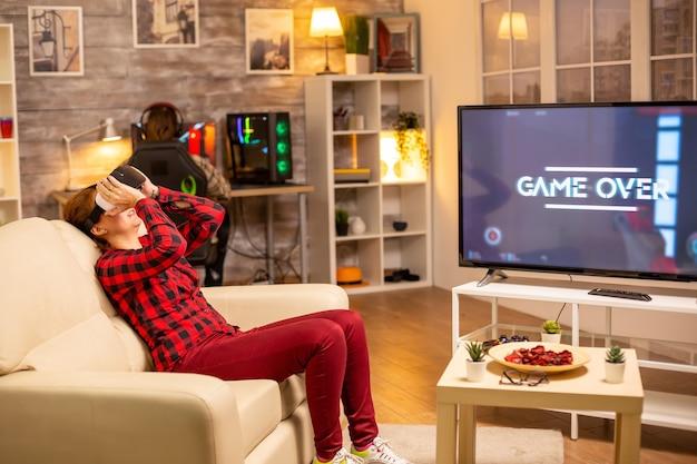 Kobieta przegrywająca w gry wideo podczas grania w zestaw słuchawkowy wirtualnej rzeczywistości późno w nocy w salonie