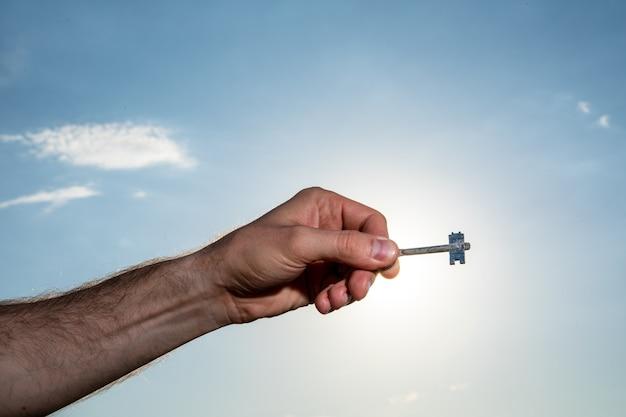 Kobieta przekazująca klucze na dramatycznych chmurach i niebie z promieniami słońca za.