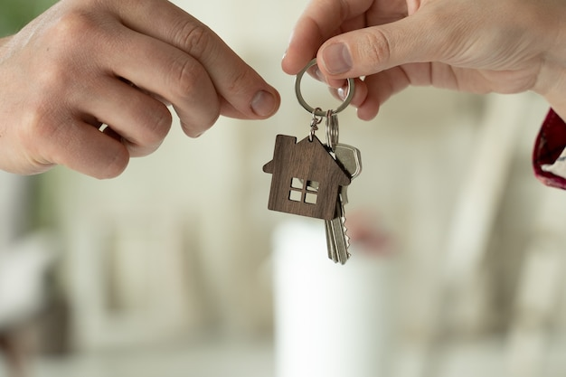 Kobieta przekazuje w rękach klucze do nowego domu