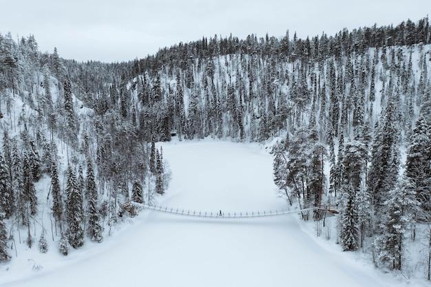 Kobieta przekraczająca wiszący most w zaśnieżonym parku narodowym oulanka, finlandia. zdjęcia z drona
