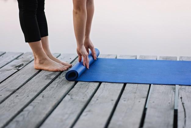 Kobieta przekręca matę do jogi na zewnątrz w pobliżu rzeki na drewnianym molo w godzinach porannych