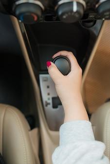 Kobieta przełącza zbliżenie automatycznej skrzyni biegów. zbliżenie na adm kierowcy obejmuje tryb napęd na dźwigni zmiany biegów automatyczna skrzynia biegów części wnętrza samochodu