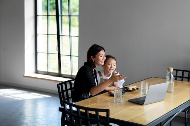 Kobieta przeprowadza wideorozmowę z mężem obok córki w domu