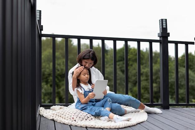 Kobieta przeprowadza wideorozmowę z mężem przy córce na świeżym powietrzu