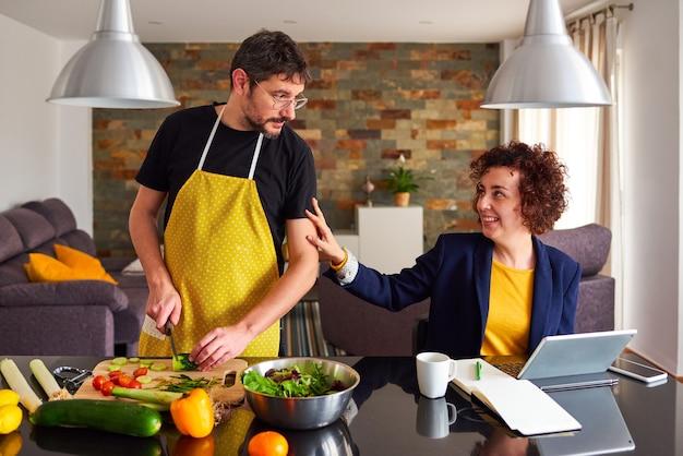 Kobieta przerywa pracę zdalną, aby pogłaskać męża przygotowującego jedzenie