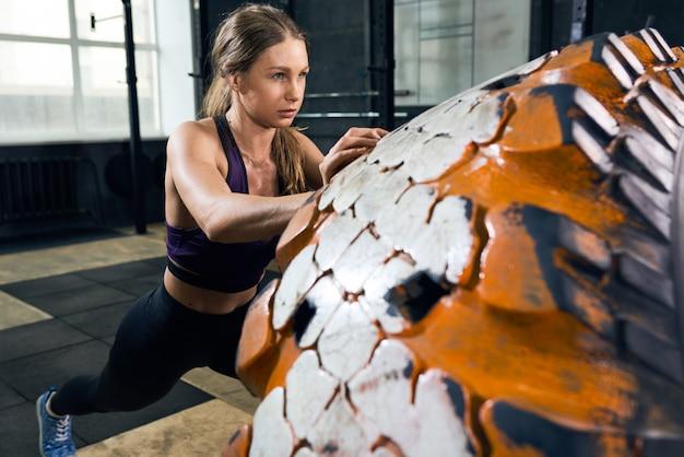 Kobieta przerzucanie opon w siłowni