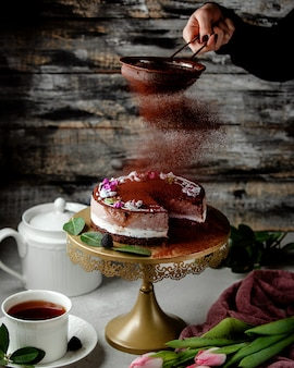 Kobieta przesiać kawę w proszku nad ciastem kakaowym z kremem waniliowym i kawowym