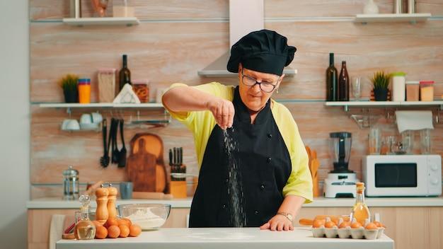 Kobieta przesiewa mąkę na drewnianym stole w nowoczesnej kuchni. szczęśliwy starszy piekarz z bonete przygotowujący surowe składniki do pieczenia domowego ciasta posypującego, ręcznie przesiewający mąkę pszenną
