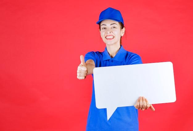 Kobieta przewodnik w niebieskim mundurze trzyma białą prostokątną tablicę informacyjną i pokazuje znak przyjemności.