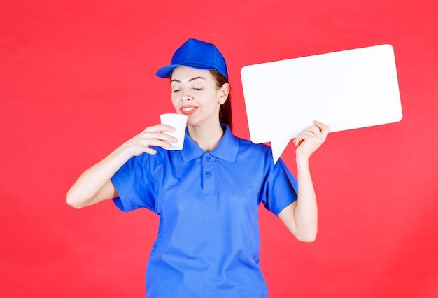 Kobieta przewodnik w niebieskim mundurze trzymająca białą prostokątną tablicę informacyjną i jednorazową filiżankę napoju.