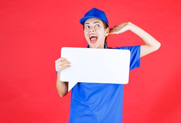 Kobieta przewodnik w niebieskim mundurze trzymająca białą prostokątną tablicę informacyjną, otwierającą uszy i krzyczącą.