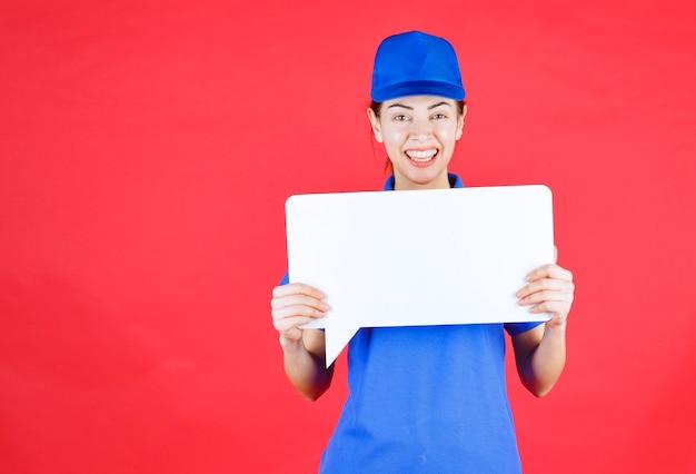 Kobieta przewodnik w niebieskim mundurze trzymająca białą prostokątną tablicę informacyjną.
