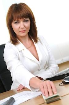 Kobieta przy biurku trzyma pieniądze z łapówki