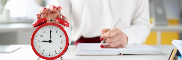 Kobieta przy biurku trzyma rękę na czerwonym budziku i robi wpisy w czasie pamiętnika