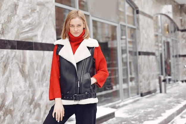 Kobieta przy budynku. nastrój noworoczny. pani w czarnej kurtce.