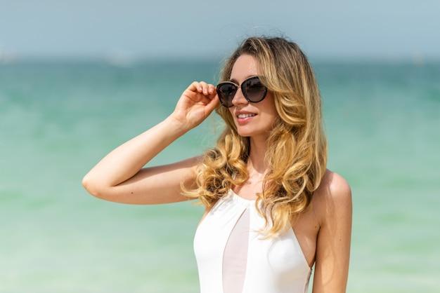 Kobieta przy dubaj plażą w białych swimsuits
