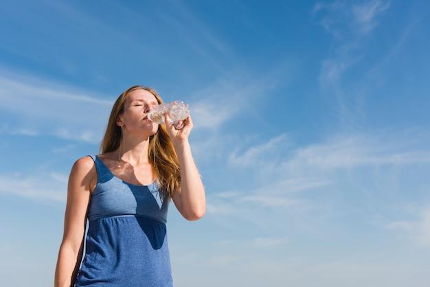 Kobieta przy nieba tła napoju wodą outdoors
