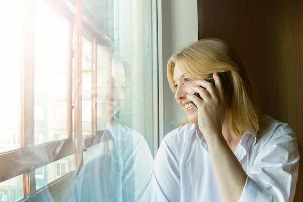 Kobieta przy oknie. słoneczny poranek.
