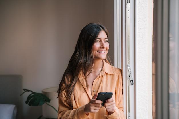Kobieta przy oknie w domu przy użyciu telefonu komórkowego