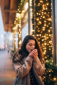 Kobieta przy oświetlonej gablocie na ulicy miasta