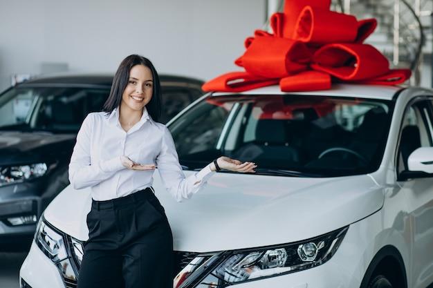 Kobieta przy samochodzie z dużą czerwoną kokardą