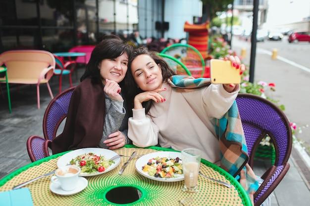 Kobieta przy selfie z mamą, siedząc w kawiarni i pozowanie
