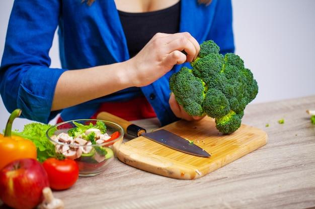 Kobieta przy stole gospodarstwa brokuły na powierzchni owoców i warzyw