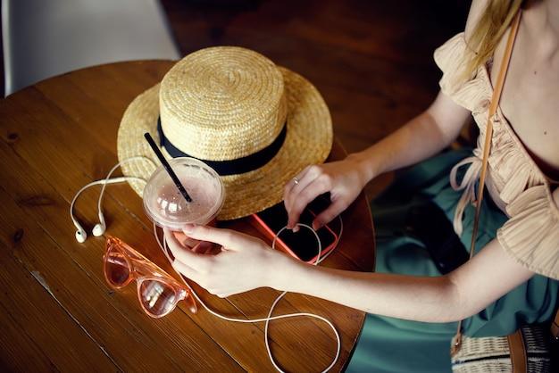 Kobieta przy stole w kawiarni wakacje słuchawki kapelusz styl życia wnętrze. wysokiej jakości zdjęcie