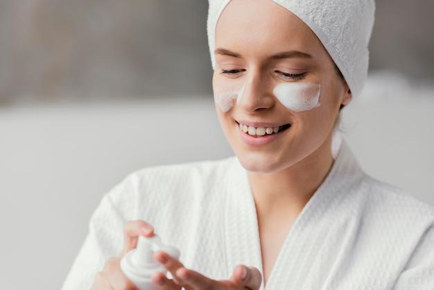 Kobieta przy użyciu białego kremu do twarzy