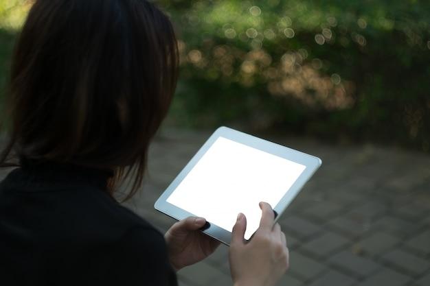 Kobieta przy użyciu tabletu w ogrodzie