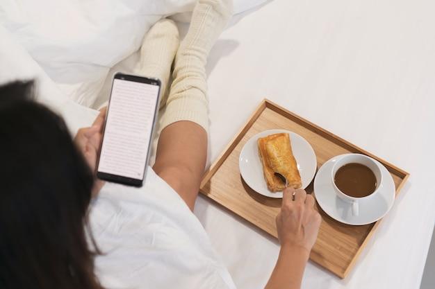 Kobieta przy użyciu telefonu komórkowego podczas jedzenia śniadania na łóżku. technologia, styl życia, koncepcja żywności.