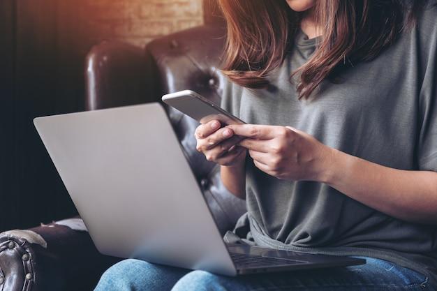 Kobieta przy użyciu telefonu komórkowego podczas pracy na laptopie
