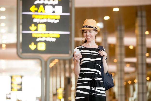 Kobieta przy użyciu telefonu komórkowego w porcie lotniczym