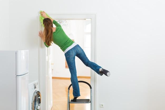 Kobieta przy wiosennym cleaning pracuje niebezpiecznie