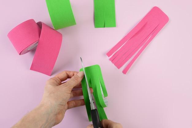 Kobieta przycina różowe taśmy w kształcie ośmiornicy, aby skorygować sylwetkę i wyeliminować cellulit. korekcja ciała i przyspieszenie odpływu limfy.