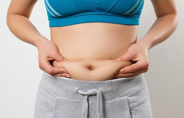 Kobieta przyciska palce do fałd tłuszczu po bokach brzucha