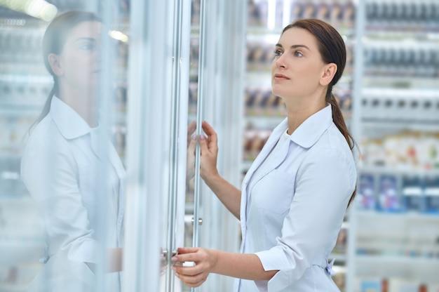 Kobieta przyglądająca się z bliska półkom aptecznym