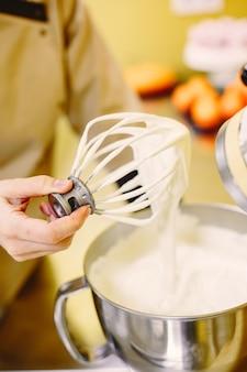 Kobieta przygotowuje ciasta. cukiernik w płaszczu.