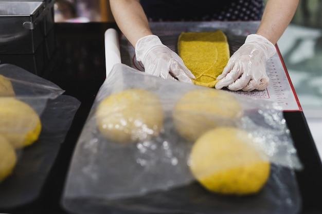 Kobieta przygotowuje ciasto chlebowe na stole w kuchni