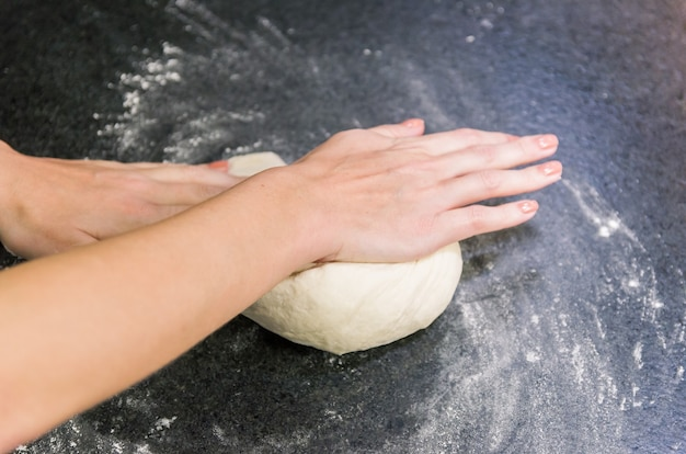 Kobieta przygotowuje ciasto do pizzy na stole z czarnego granitu