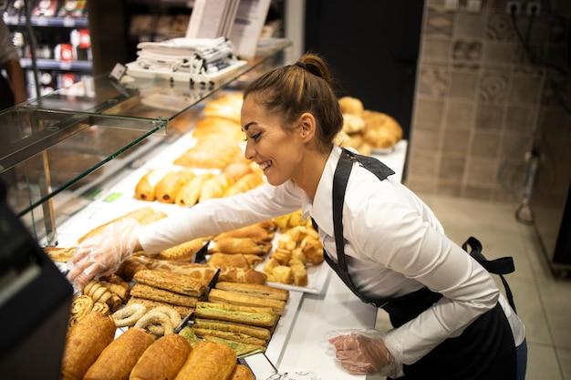 Kobieta przygotowuje ciasto do sprzedaży w dziale piekarni supermarketu