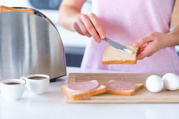 Kobieta przygotowuje i rozprowadza masło na grzankach chlebowych na śniadanie w kuchni w domu wcześnie rano