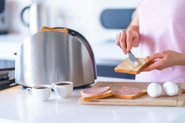 Kobieta przygotowuje i rozprzestrzenia masło na grzankach chlebowych na śniadanie w kuchni w domu wcześnie rano