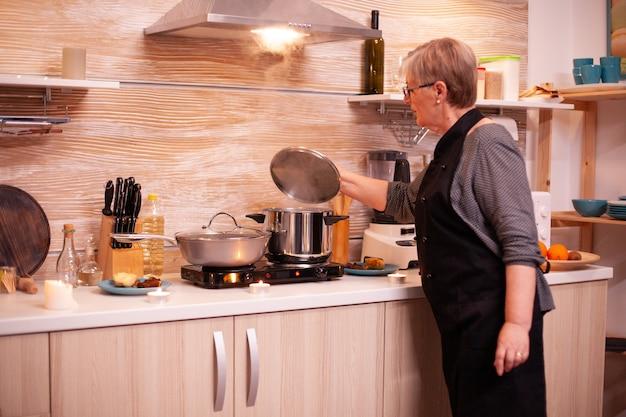 Kobieta przygotowuje jedzenie na kuchence gazowej na romantyczną kolację z mężem. emerytowana kobieta gotuje pożywne jedzenie dla niej i mężczyzny z okazji rocznicy związku.